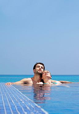 Couple relaxing in infinity pool, Couple relaxing in infinity pool