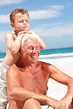 Older man with grandson on beach, Older man with grandson on beach
