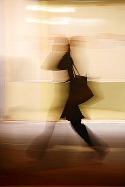 woman shopper feet legs walking in street in town at night