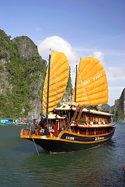 Traditional style cruising junk sails close by floating fishermens village beneath rocky islands of Halong Bay Vietnam