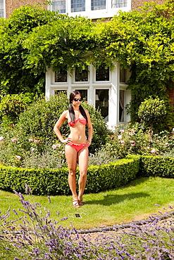 Woman in bikini standing in garden. Woman in bikini standing in garden