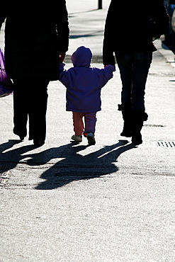 people with baby walking along street