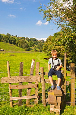 A seven year old boy sitting on a style in Swaledale in North Yorkshire, England, Britain, Uk