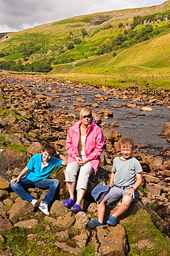 A mother and her two sons at the river Swale at Muker in Swaledale in North Yorkshire, England, Britain, Uk