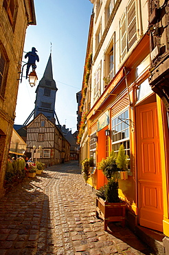 Narrow street with colourful shops looking towards the Bell tower of the Wooden Church of St Terezza - Market Square Honfleur Normandy France