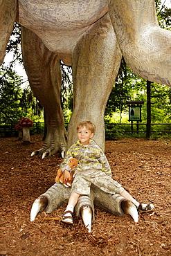 Boy with his teddy lion sitting on a leg of a dinosaur