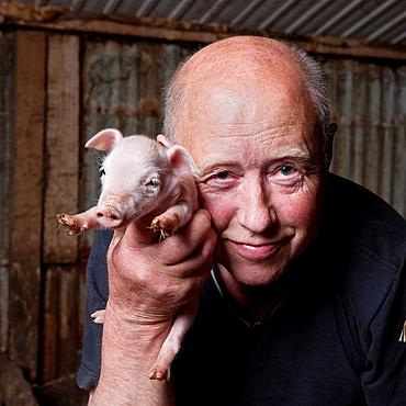 Pig farmer with piglet, Hornafjordur, Iceland