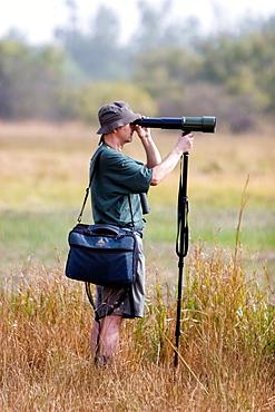 Bird watcher scans grassland mud flats with tlescope on monopod near Tendaba Camp The Gambia