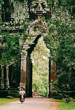 A lone lady riding a motorbike without a helmet through one of the old stone gateways of the Angkor Wat Temple complex in Cambodia, a UNESCO World Heritage Site