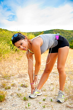 17 years old hispanic girl in fitness outfit stretching and getting ready to work out outdoors