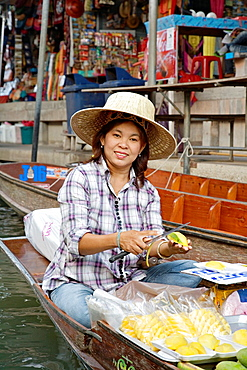 Selling food and souvenirs at the Damnoen Saduak floating market located about 62 miles outside of Bangkok Thailand