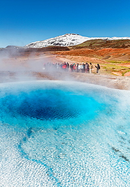 Tourist waiting for Strokkur geyser to erupt, Iceland Strokkur is a fountain geyser in the geothermal area beside the Hvita River  It is one of Iceland´s most famous geysers, erupting about every 4-8 minutes and 15 - 20 m high, sometimes up to 40 m high