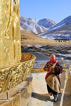 China, Gansu, Amdo, Xiahe, Monastery of Labrang Labuleng Si, Tibetan devotee in prayer on top of Gongtang chorten