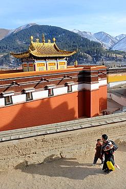 China, Gansu, Amdo, Xiahe, Monastery of Labrang Labuleng Si, Losar New Year festival, Tibetan pigrim and child doing the kora circumambulation around the monastery