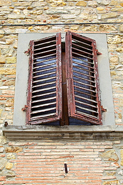 Rustic Weathered Brown Window Shutters against a Stone and Brick Wall