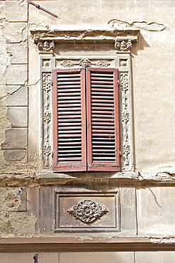 Brown Wood Shutters on a Weathered Plaster Wall in Tuscany