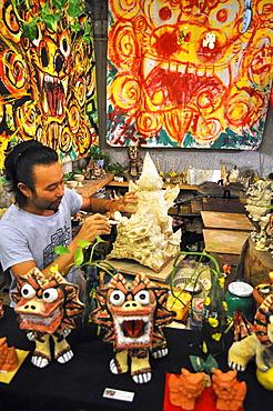 Naha, Okinawa, Japan, artisan making Shisa statuettes in his shop along Okiei-dori Shisa is a traditional Ryukyuan decoration resembling a cross between a lion and a dog, from Okinawan mythology