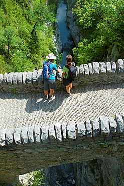 Hikers walking on San Urbez Bridge above Bellos river, in Anisclo Valley, canyon belonging to Ordesa y Monte Perdido National Park Pyrenees Fanlo Huesca province Aragon Spain