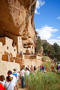 Tourists visit Cliff Palace cliff dwellings in Mesa Verde National Park, Colorado