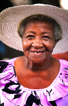 Colorful local woman in hat smiling portrait in the beautiful village of La Digue in the Seychelles Islands off of Africa