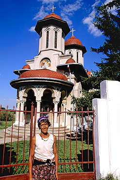 Native woman in front of an old and beautiful Romanian Orthodox Church in Giuren Romania