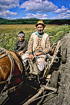 Man and son on wagon with horse in rural Macedonia