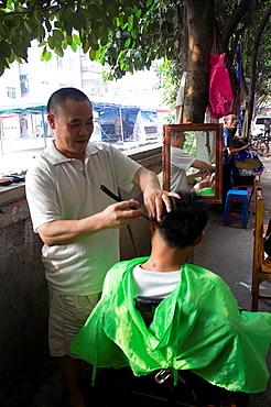 Street barbers at outskirt of Guangzhou, China.