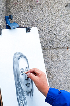 Close view of an artists hand drawing a portrait. Plaza Mayor, Madrid, Spain.