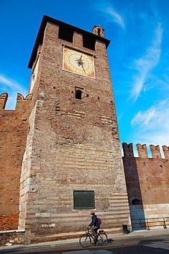 Cyclist on Corso Cavour outside clock tower of Castelvecchio fortress 1355 Verona city the Veneto region northern Italy Europe