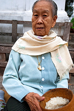 Elderly woman with basket of sticky rice for monks Luang Prabang Laos PDR