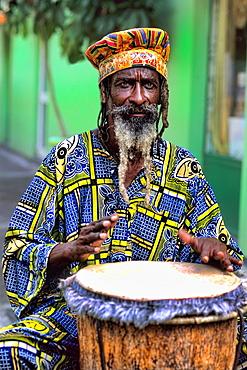 Colorful Rasta Jamaican Reggae performer on drum in costume at Harbour in St John Antigua