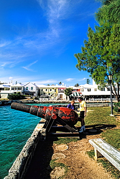 Couple at cannon at Colorful St George Harbour in Bermuda