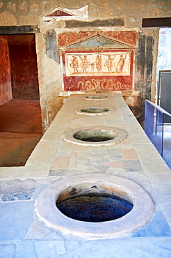 The Thermopolium of Lucius Vetutius Placidus on the Via del Abbondante, with the serving counter with holes that contained amphora of food for sale The Thermopolium was an eating & drinking house The painting depicts at the centre the God of the patron
