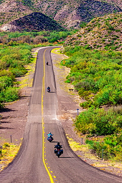 Motoryclists ride down a long straight road FM 170, the Camino del Rio, Big Bend Ranch State Park, Texas USA