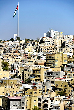Panoramic view of Amman, Jordan and the National flag.