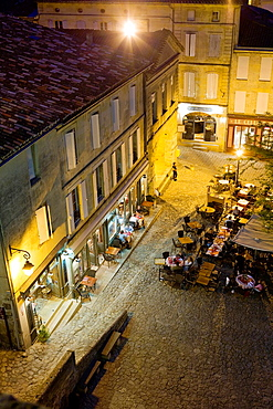 Restaurants and people dining outdoors in Place de L'eglise Monolithe, Saint-Emilion, near Bordeaux, in the Dordogne River Valley, Gironde region, Acquitaine, France, night