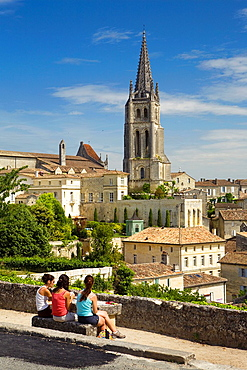 Saint-Emilion, in the Dordogne River Valley, Gironde region, Acquitaine, France, overview with houses and tower of Romanesque monolithic church 'L'Eglise Montlithe', three young women playing cards, May