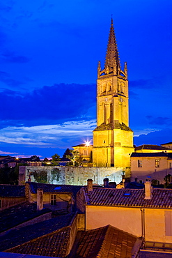 Saint-Emilion, in the Dordogne River Valley, Gironde region, Acquitaine, France, Romanesque tower of the monolithic church 'L'Eglise Monolithe', house roofs, at dusk