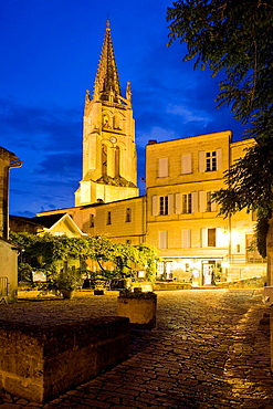 Saint-Emilion, near Bordeaux, in the Dordogne River Valley, Gironde department, Acquitaine, France: tower of the Romanesque monolithic church 'L'Eglise Monolithe', restaurants, and houses, night