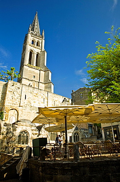 Men setting up umbrellas for outdoor restaurants in Place de L'Eglise Monolithe, Monolithic Church in background, Saint-Emilion, Gironde department, Acquitaine, France, early morning, May
