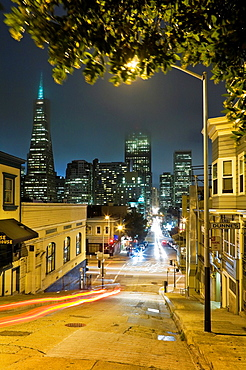 Kearny Street crossing Broadway, San Francisco, California, USA, night, fog in sky, Trans-America pyramid, Bank of America building, and other high-rise office buildings, Victorian style house on right