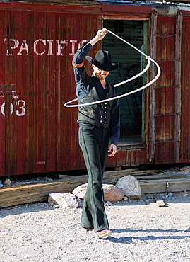 A travelling lasso artist at a spontaneous performance in the ghost town of Rhyolite Rhyolite's glory days of goldmining lasted only a few years from 1905 on It is located in Nevada 35 miles from the Furnace Creek Visitor Center in Death Valley National Park in California Rhyolite, Nevada, USA