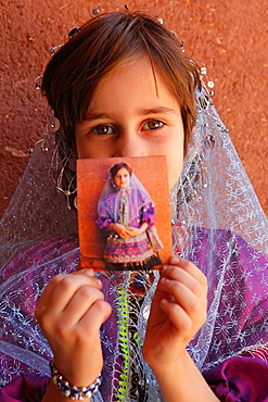 Portrait of a young iranian girl showing a Polaroid, Abyaneh, Iran
