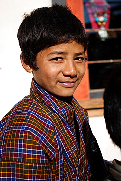 Portrait of a boy in traditional dress, a village of Punakha Valley, Bhutan, Asia.