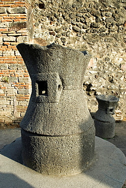 millstone or Catullus inside the Bakery or Pistrinum, archeological site of Pompeii, province of Naples, Campania region, southern Italy, Europe