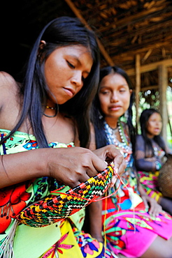 Esilda and her friends making basket, young teenagers of Embera native community living by the Chagres River within the Chagres National Park, Republic of Panama, Central America