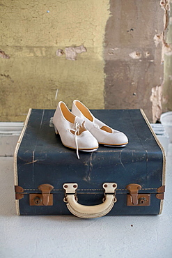Shoes sitting on antique suitcase