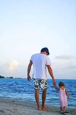 Father and toddler daughter on beach