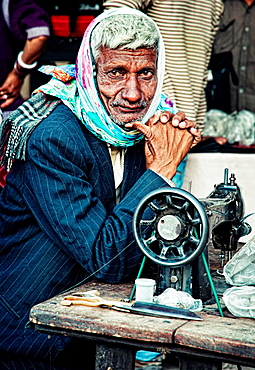 Portrait of a tailor sitting at his sewing table Jodhpur, Rajasthan, India