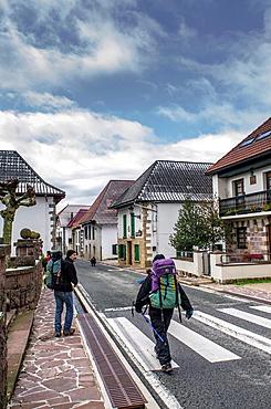 Pilgrims walking on road in Burgui village, Navarre Pyrenees, Spain